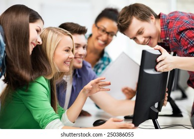 education concept - students looking at computer monitor at school