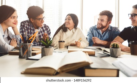 Education concept. University students preparing for exam, talking and drinking coffee in library