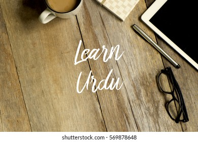 Education concept.Top view of tablet, glasses. notebook pen and cup of coffee with LEARN URDU  on wooden background.It is the national language and of Pakistan, and five states of India in 2017. - Shutterstock ID 569878648