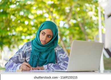Education concept: Young Muslim girl is writing while thinking