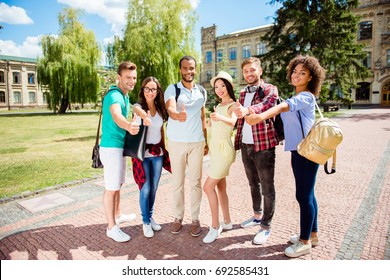 Education is cool! Successful future for smart youth! Six attractive young bachelors are welcoming in their university, standing near the building, gesturing thumbups, smiling, wearing casual smart