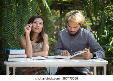 Education couple sitting at nature home garden, time to reading and tutorial for exam together. Education people concept.