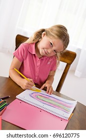 Education: Cute Girl Drawing Rainbow At Table With Colored Pencil