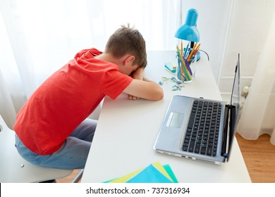 education, cyberbullying and people concept - tired or sad student boy with laptop computer lying on desk at home suffering from bullying