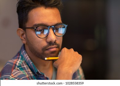 education, deadline and people concept - close up of creative man in glasses working at night office and thinking