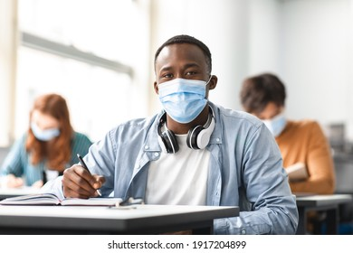 Education During Pandemic Concept. Portrait of black male student sitting at table in classroom at university, wearing protective medical face mask, writing in notebook, looking posing at camera