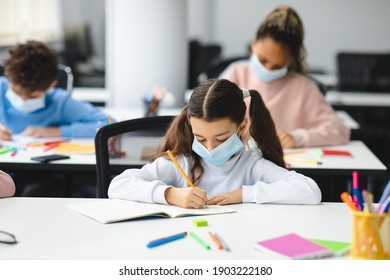 Education During Pandemic. Small girl sitting at desk in classroom at school or kindergarten, wearing disposable surgical face mask, writing or drawing in notebook. New Normal, Safe Learning