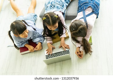 Education, E-Learning and digital lifestyle Concept.Three happy kids learning on notebook computer together.Kindergarten children learning how to use computers.