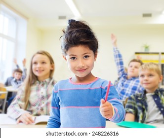 education, elementary school and children concept - happy little student with pen girl over classroom and classmates background