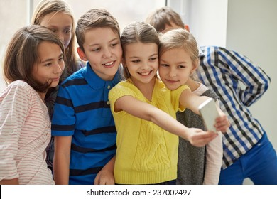 education, elementary school, drinks, children and people concept - group of school kids taking selfie with smartphone in corridor