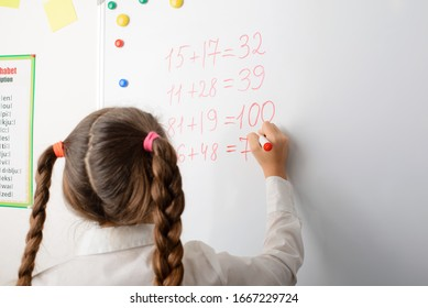 Education, elementary school, learning, math and people concept. Clever female learner of primary school writing on board some mathematical equations, counting numbers