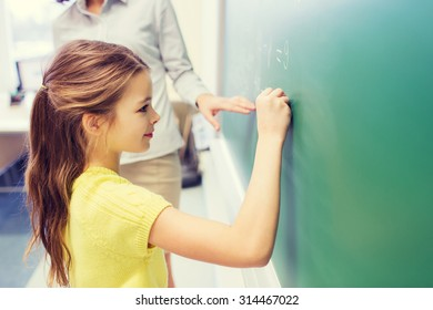 education, elementary school, learning, math and people concept - little smiling schoolgirl writing numbers on green chalk board in classroom