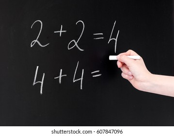education, elementary school, learning, math and people concept - hand with chalk writing numbers on blackboard