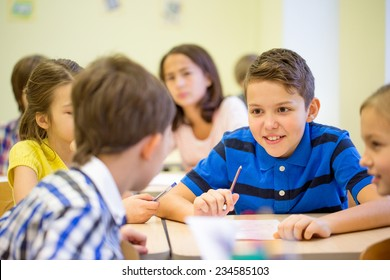 education, elementary school, learning and people concept - group of school kids talking during lesson in classroom