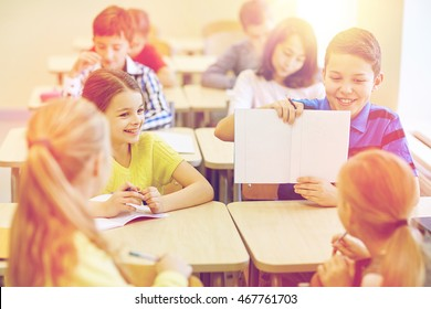 education, elementary school, learning and people concept - group of school kids with pens writing test and showing notebook in classroom