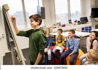 education, elementary school, learning and people concept - happy student boy with marker writing on flip board