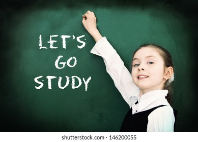 Education. Elementary school student at the blackboard. School concept - Let's go study