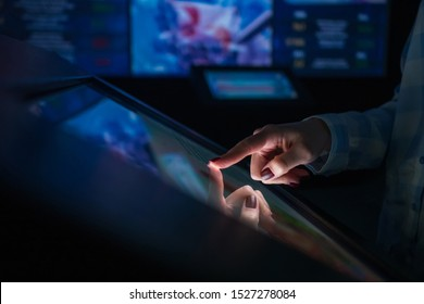 Education, entertainment, learning, technology concept - woman using interactive touchscreen display of electronic kiosk at modern museum or exhibition - scrolling and touching - side close up view
