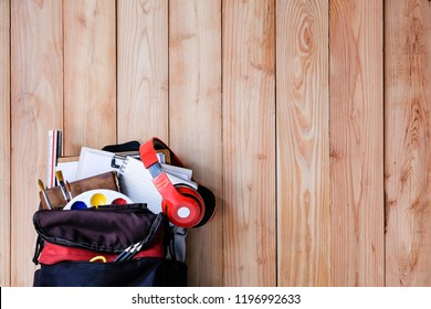 Education equipment object on school bag with a wooden background.