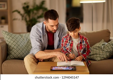 education and family concept - father and son with book and tablet computer doing homework together at home in evening
