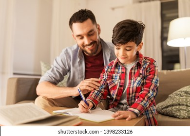 education, family and homework concept - happy father and son with book writing to notebook at home