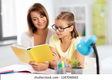 education, family and learning concept - mother and daughter doing homework together and reading book at home