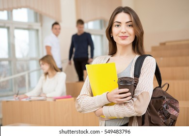 Education first. Beautiful female college student holding her books smiling happily standing in an auditorium people education learning high school program smart teenager concept copyspace