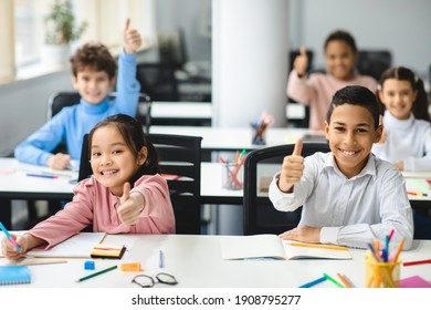 Education Is Fun Concept. Diverse group of happy smiling international classmates sitting at desks in classroom and showing thumbs up sign gesture, children enjoying studying at junior school
