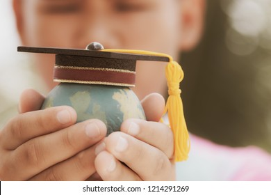 Education in Global, Graduation cap on top model Earth in student hands. Concept of abroad international Educational and save world. Back to School and Studies lead to success in world wide.