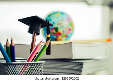 Education Graduate study concept: Black Graduation hat on pencils, blur of europe earth world globe on stack textbook at university classroom. Ideas knowledge learning success, Back to School