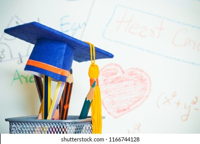 Education Graduate study concept: Graduation hat on pencils with formula arithmetic equation graph on projecter screen at university classroom. Ideas for knowledge learning success and Back to School