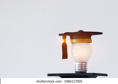 Education or Graduate study Creative concept: Hands holding light bulb with Graduated hat on gray background. Ideas with innovation creativity for Educational successs studies world. back to School