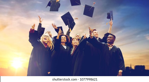 education, graduation and people concept - group of happy international students in bachelor gowns throwing mortar boards up in the air