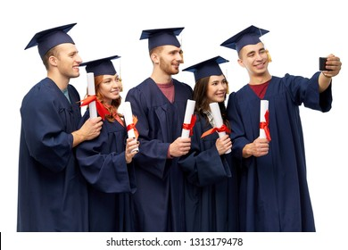 education, graduation and people concept - group of happy graduate students in mortar boards and bachelor gowns with diplomas taking selfie by smartphone over white background