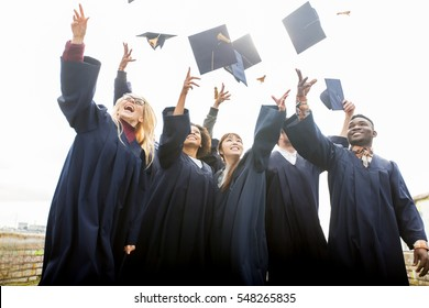 education, graduation and people concept - group of happy international students in bachelor gowns throwing mortar boards up