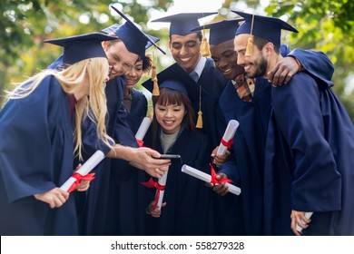 education, graduation and people concept - group of happy international students in mortar boards and bachelor gowns with diplomas and smartphone