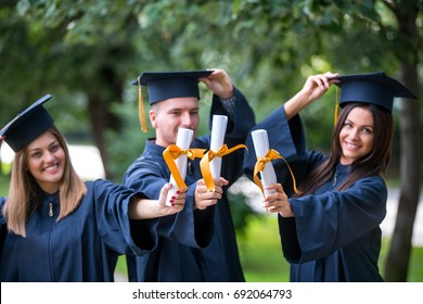 education, graduation, people concept - group of happy international students in mortar boards and bachelor gowns with diplomas