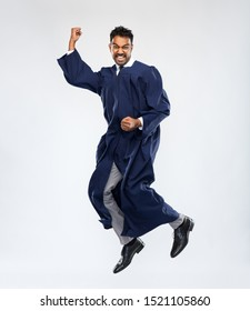 education, graduation and people concept - happy smiling indian male graduate student in bachelor gown celebrating success and jumping over grey background