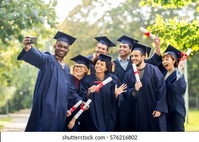 education, graduation, technology and people concept - group of happy international students in mortar boards and bachelor gowns with diplomas taking selfie by smartphone outdoors
