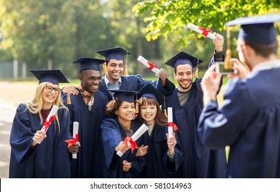 education, graduation, technology and people concept - group of happy international students in mortar boards and bachelor gowns with diplomas taking picture by smartphone outdoors