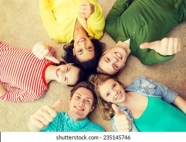 education and happiness concept - group of young smiling people lying down on floor in circle and showing thumbs up