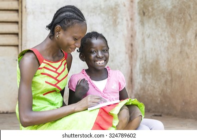 Education Happiness Symbol: African schoolgirls smiling and laughing in the streets of Bamako, whilst learning and studying for school lessons. Candid photo outside of their classroom.