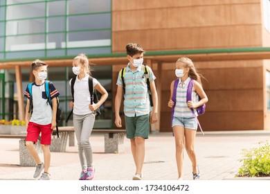 concept d'éducation, de soins de santé et de pandémie - groupe d'élèves de l'école primaire portant des masques médicaux de protection contre la maladie virale avec des sacs à dos marchant et parlant à l'extérieur