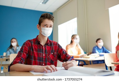 education, healthcare and pandemic concept - group of students wearing face protective medical mask for protection from virus disease with books at school lesson