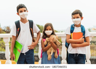 education, healthcare and pandemic concept - group of elementary school students wearing protective medical face masks for protection against virus diseases with backpacks walking