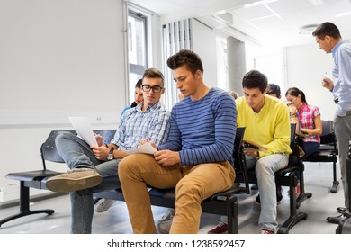 education, high school and people concept - group of students with papers in lecture hall taking notes