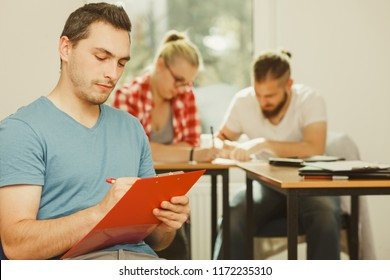Education, high school, teamwork and people concept - student boy with notebook sitting in front of students her group mates in classroom