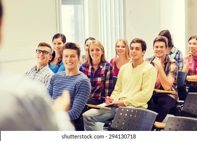 education, high school, teamwork and people concept - group of smiling students with notebooks and teacher in classroom