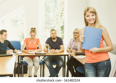Education, high school, teamwork and people concept - smiling student girl with notebook standing in front of students her group mates in classroom