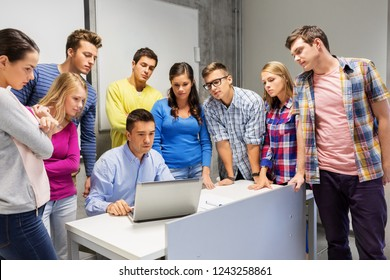 education, high school, technology and people concept - group of students and teacher with laptop computer in classroom